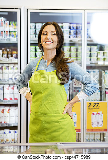 Saleswoman With Hands On Hip Against Refrigerator - csp44715989