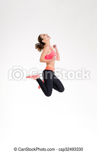 Atractiva y excitada chica en traje deportivo saltando de alegría - csp32493330
