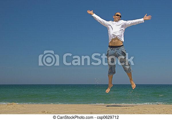 Hombre saltando en la playa - csp0629712