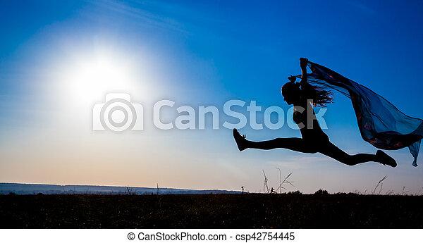 Silueta de saltarina contra el amanecer - csp42754445