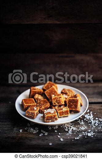 Salted caramel pieces and sea salt macro. Butter caramel candy macro. - csp39021841