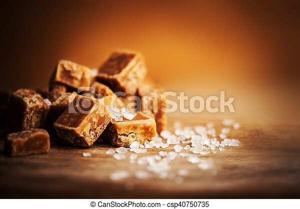 Salted caramel pieces and sea salt. Golden Butterscotch toffee caramels. Toffees. - csp40750735