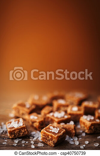 Salted caramel pieces and sea salt. Golden Butterscotch toffee caramels. Toffees. - csp40750739