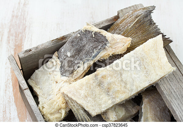salted cod fish in wooden box on white background - csp37823645