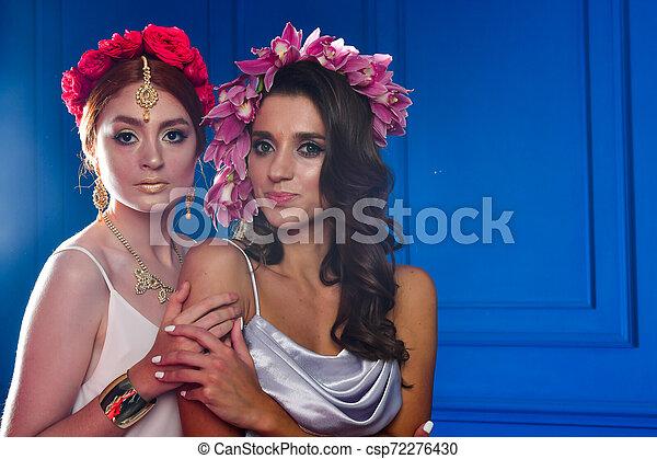 Retrato de las dos hermosas damas con flores silvestres. Elegancia. Lucha de fantasía - csp72276430