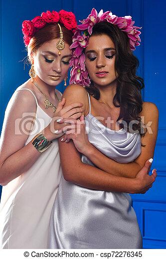 Retrato de las dos hermosas damas con flores silvestres. Elegancia. Lucha de fantasía - csp72276345