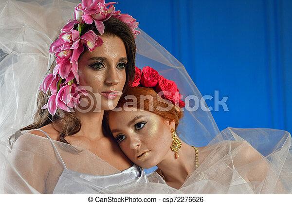 Retrato de las dos hermosas damas con flores silvestres. Elegancia. Lucha de fantasía - csp72276626