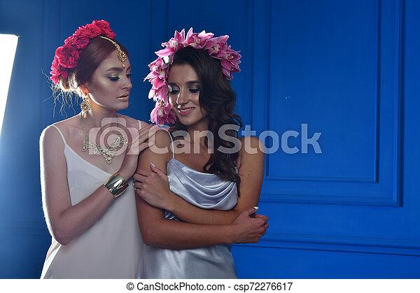 Retrato de las dos hermosas damas con flores silvestres. Elegancia. Lucha de fantasía - csp72276617