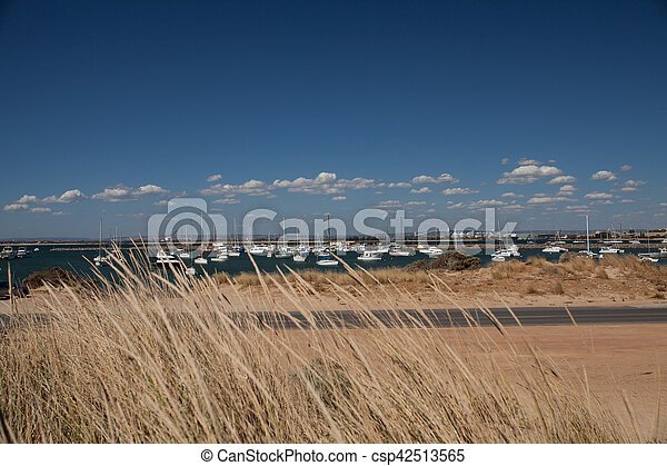 Sand dunes and a street in front of a harbor with yachts under blue sky wiith little withe clouds - csp42513565