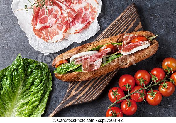 Sandwich with salad, prosciutto and mozzarella - csp37203142