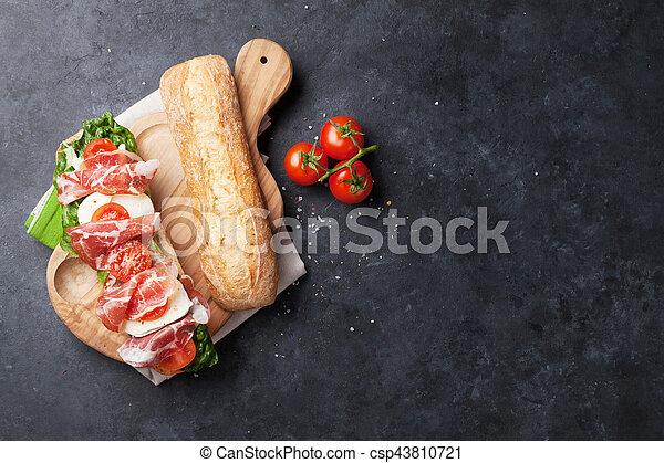 Sandwich with salad, prosciutto and mozzarella - csp43810721