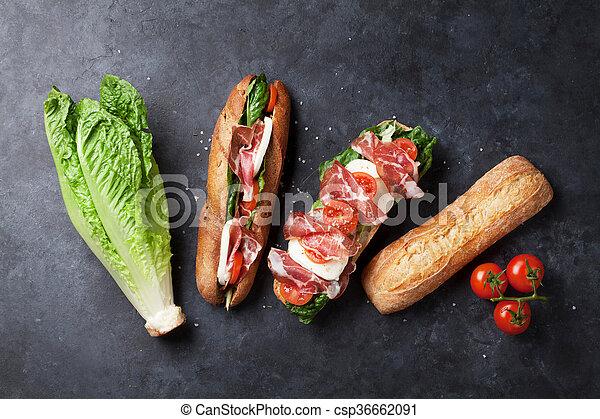 Sandwich with salad, prosciutto and mozzarella - csp36662091