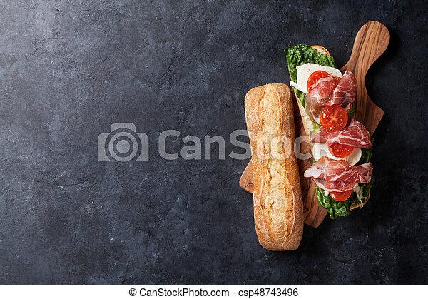 Sandwich with salad, prosciutto and mozzarella - csp48743496