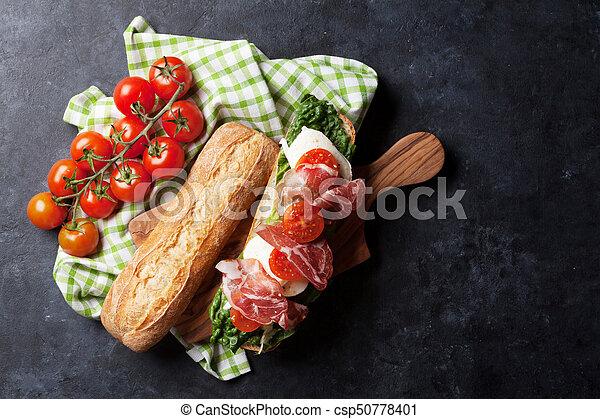 Sandwich with salad, prosciutto and mozzarella - csp50778401