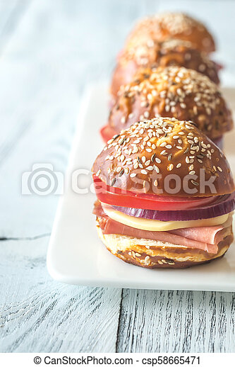 Sandwiches with cheese and ham on the plate - csp58665471