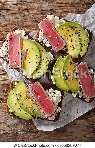 sandwiches with fried tuna in sesame, fresh avocado and cream cheese close-up. Vertical top view - csp50289077