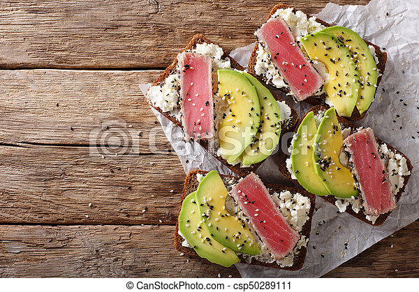sandwiches with fried tuna in sesame, fresh avocado and cream cheese close-up. Horizontal top view - csp50289111