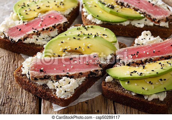 sandwiches with fried tuna in sesame, fresh avocado and cream cheese close-up. horizontal - csp50289117