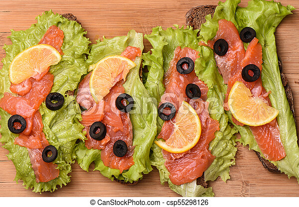 Sandwiches with red fish on a cutting board - csp55298126