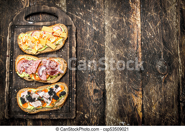 Sandwiches with seafood, salami, cheese and vegetables. - csp53509021