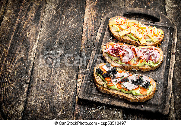 Sandwiches with seafood, salami, cheese and vegetables. - csp53510497