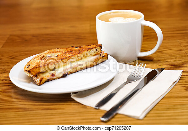 Sandwish and coffee on the wood table in the morning. - csp71205207