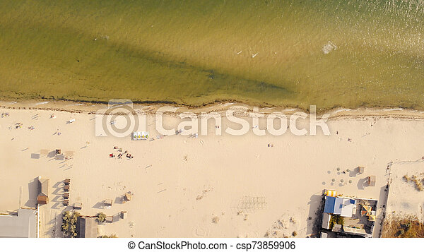 Sandy beach with sunbathing tourists, view from drone. - csp73859906