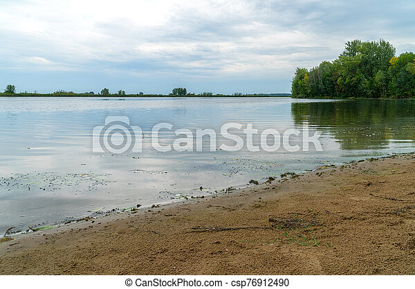 Sandy shore of the lake with a quiet surface of water under cloudy overcast sky - csp76912490