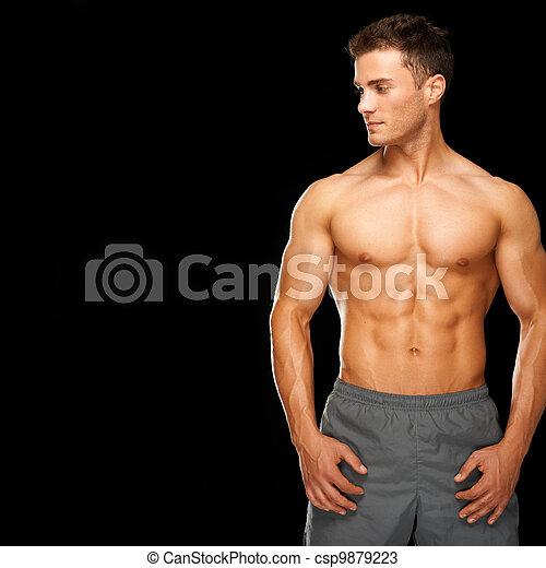 Hombre deportivo y musculoso sano aislado en negro - csp9879223