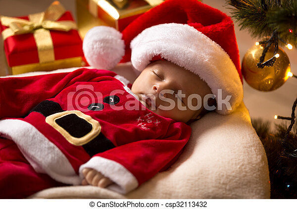 Newborn santa baby sleeping with christmas presents at living room.