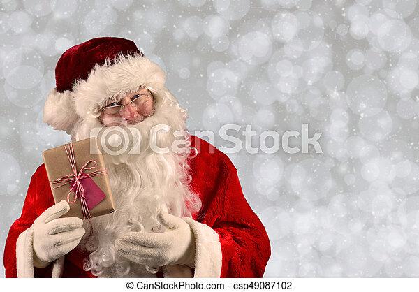 Santa Claus Holding a Christmas Present - csp49087102