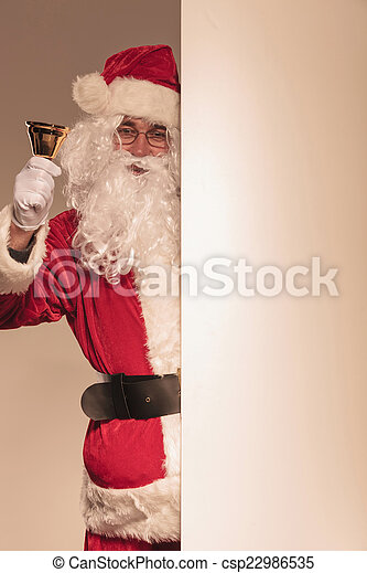 Santa Claus holding a golden bell in his hand - csp22986535