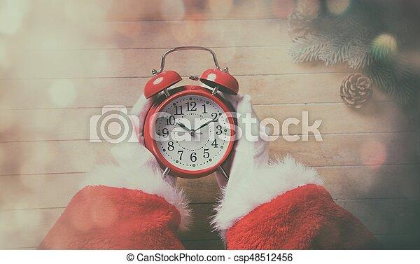 Santa Claus holding Chrstmas alarm clock - csp48512456