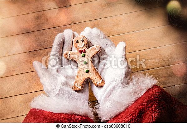 Santa Claus holding Chrstmas cookie - csp63608010