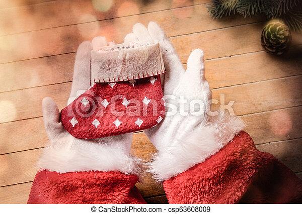 Santa Claus holding Chrstmas sock - csp63608009