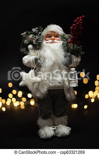Santa Claus shot against dark background with magical golden bokeh - csp63321269