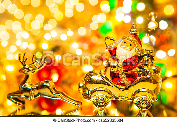 Santa Claus with gifts on car with christmas deer, on bokeh background - csp52335684