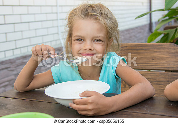 Satisfied six year old girl at the table in the courtyard eating porridge - csp35856155