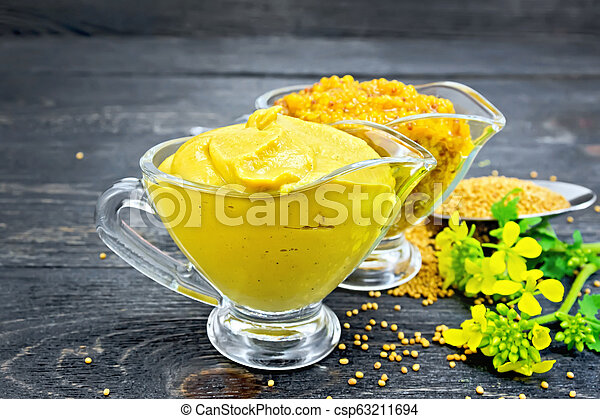 Sauce mustard in two sauceboats with flower on board - csp63211694