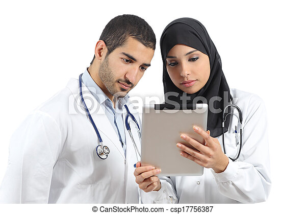 Saudi arab doctors working with a tablet - csp17756387