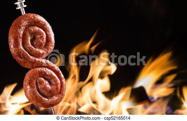 Sausage in the fire, traditional Brazilian barbecue. - csp52165014