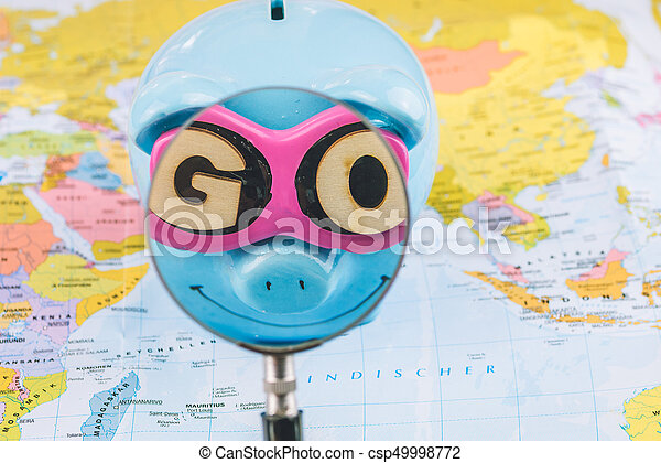 Saving piggy bank with sunglasses. Magnifier zoome into GO slogan. Pig is staying on the world map ready for travel - csp49998772