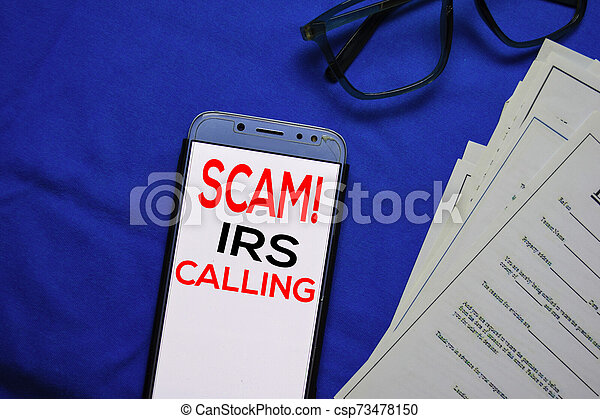 SCAM! IRS Calling text on Smart Phone isolated on office desk. - csp73478150