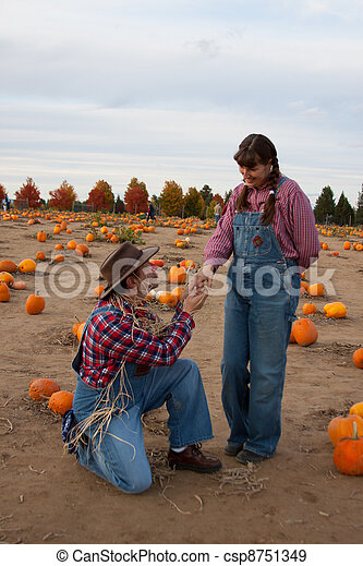 Scarecrow proposes to hillbilly woman. - csp8751349