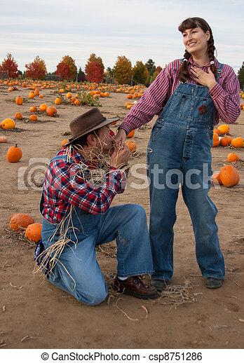 Scarecrow woos female farmer. - csp8751286