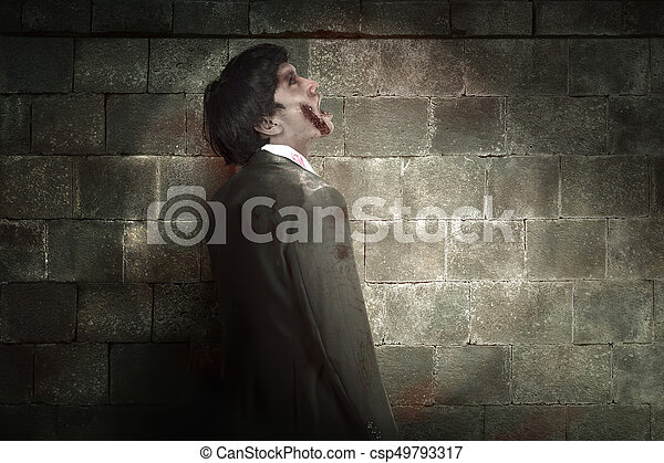 Scary asian zombie man with wounded face against black wall background