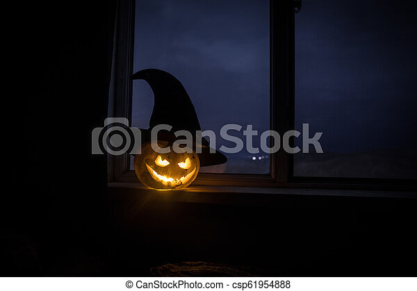 Scary Halloween pumpkin in the mystical house window at night or halloween pumpkin in night on room with blue window. Symbol of halloween in window. - csp61954888