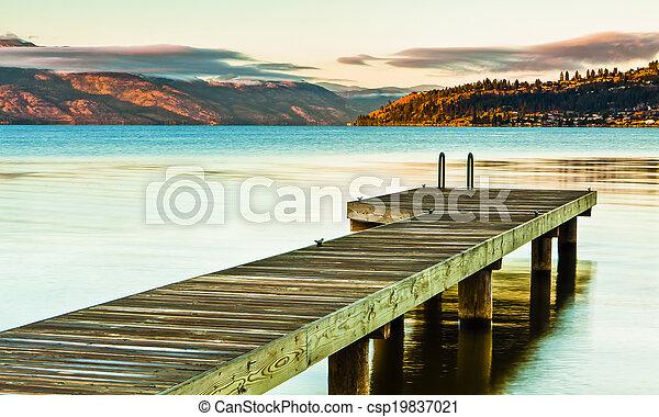 Scenic Dock on Mountain Lake at Sunrise - csp19837021