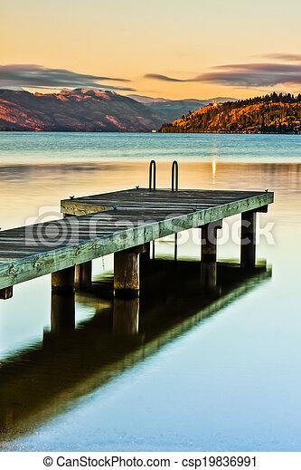 Scenic Dock on Mountain Lake at Sunrise - csp19836991