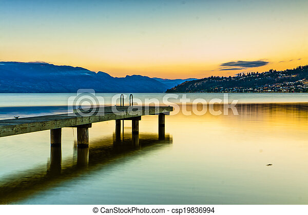 Scenic Dock on Mountain Lake at Sunrise - csp19836994